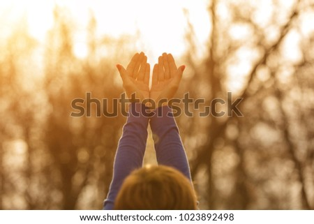 Girl with hands in the air enjoying outdoors.