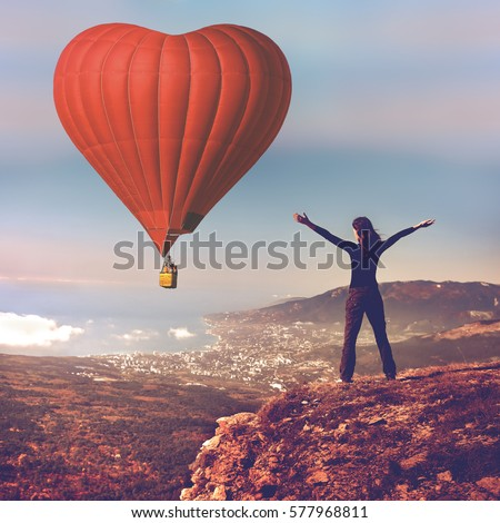 Girl with hands up stand on top of mountain looking at big red air balloon heart shape flying in blue sky. Romantic trip on Valentine's Day. Sports, travel and recreation. Nature background. Back view