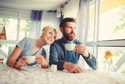 Girl with happy face fall in love with bearded man, looks at him with adoration. Couple in love drinks coffee or tea in cafe or restaurant, provence interior background. Romantic date concept.