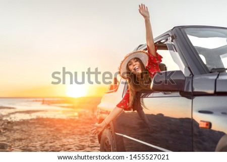 girl with happy hat at sunset on the beach with her convertible car