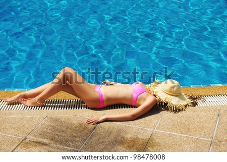 Girl with hat at tropical swimming pool