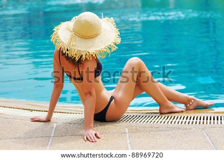 Girl with hat in tropical swimming pool