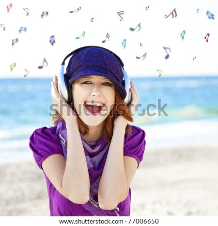 Girl with headphone and notes at the beach.