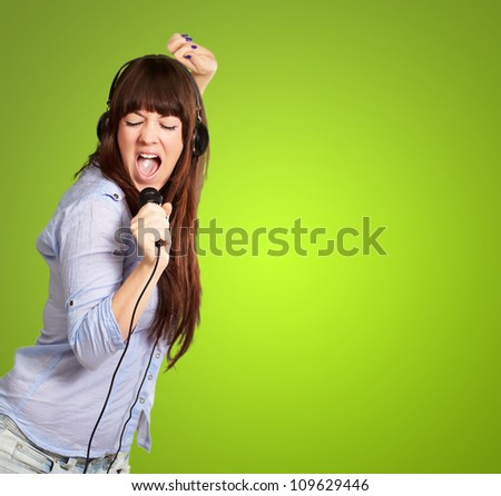 Girl With Headphone Singing On Mike On Green Background