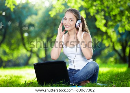 Girl with headphones and a laptop in the park