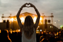 Girl with heart-shape symbol enjoying her favorite group on the concert.