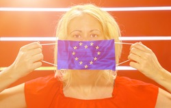 Girl with heart-shaped European flag on surgical mask. Concept outbreak and quarantine for coronavirus pandemic in Europe. Antiviral community research against COVID-19. Solidarity and union in Europe