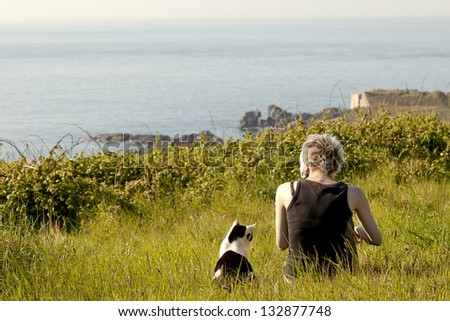 girl with her cat looking at sea