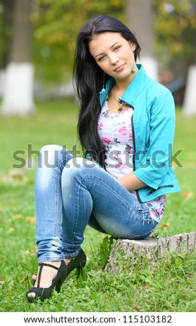 girl with her hair sitting on a stump in the park