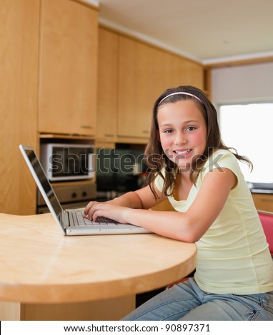 Girl with her laptop sitting at the kitchen table