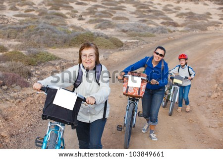 Girl with her mother and grandmother having a weekend excursion on their bikes on a summer day in beautiful landscape