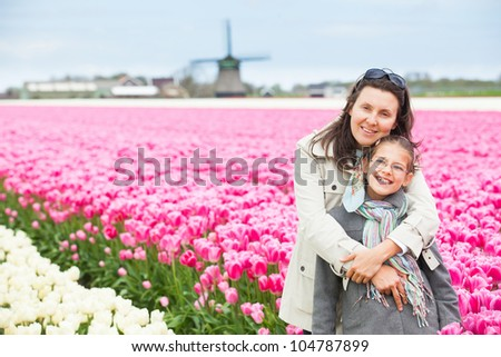 Girl with her mother walks between of the purple tulips field