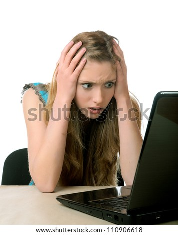 girl with horror looks at the laptop screen