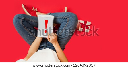 girl with ipad in her hands, gifts, discounts, sitting on an isolated red background, Lovers day concept,Valentine's Day. #1284092317
