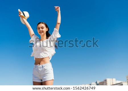 girl with joy and expression of victory raised her hands up on the background of the beach and buildings