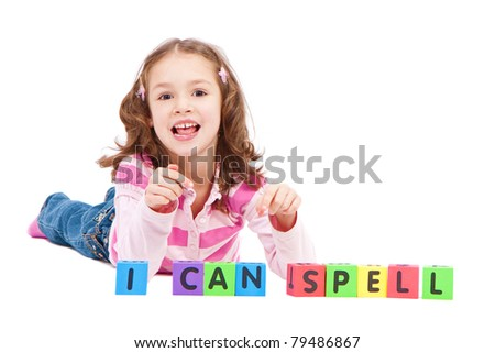 Girl with kids blocks saying I can spell. Isolated on white.