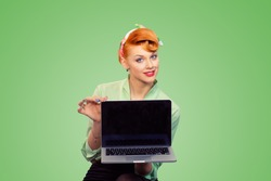 Girl with laptop. Closeup red head beautiful young woman pretty smiling pinup girl in button shirt holding pc computer smiles looking at camera retro vintage hairstyle on green Internet problem solved