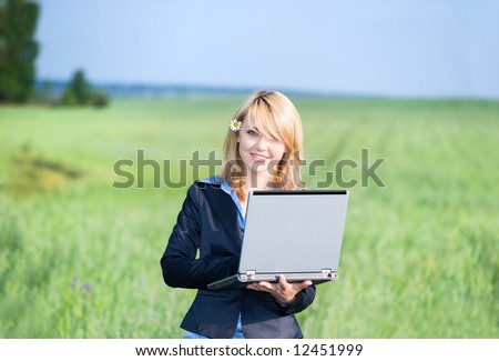 Girl with laptop stay on meadow at the noon