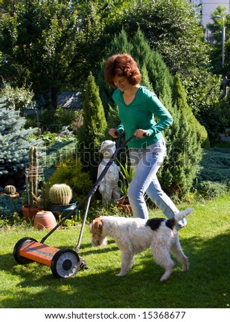 Girl with lawn mover and a small dog in the garden