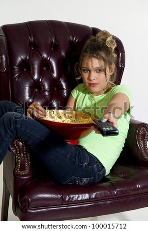 Girl with legs hanging over wing back chair watching TV with remove and bowl of popcorn