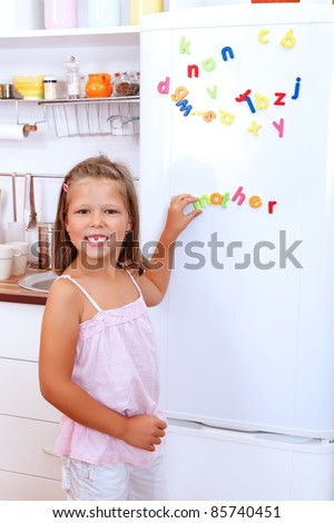 Girl with letter fridge magnets in the kitchen