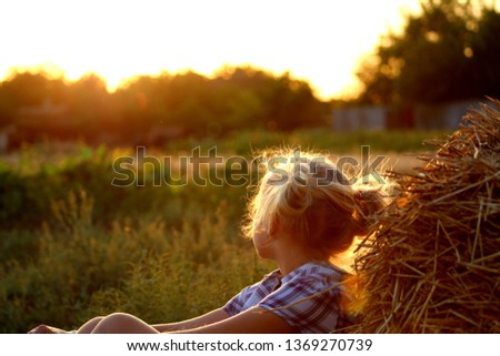 Girl with light hair in a dress check on a background rural nature near a hayloft in a summer evening somewhere on Ukraine, selective focus.
