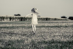 girl with long blond hair dancing alone in rural path in countryside monochrome
