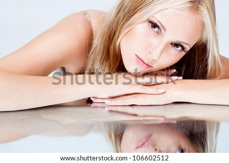 girl with long hair lying on a mirror