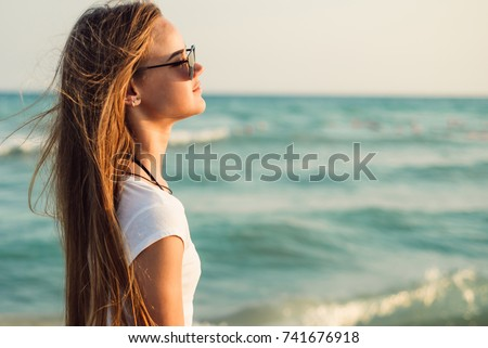 Girl With Long Hair on the background of the sea sunset  #741676918