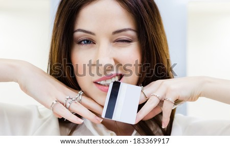 Girl with lots of rings on hands keeps credit card. Concept of wealth and luxurious life