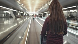 Girl with Luggage Cart Walking Airport Speedwalk. Back View of Brunette Woman with Truck. Airplane Passenger Strolling on Travelator. Modern International Terminal Shallow Focus.