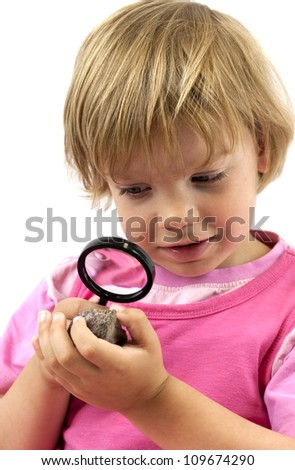 Girl with magnifying glass studying a rock