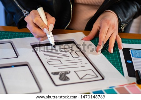 Girl with manicure develops applications for mobile devices. Application design for smartphones. The designer is working on a new gadget.