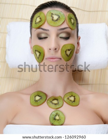 Girl with mask from kiwi on face