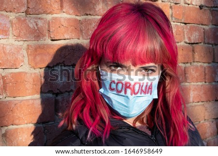 Girl with mask to protect her from Corona virus. Corona virus pandemic. Corona written on mask. Woman with mask standing next to brick wall. Beautiful red haired girl with medical mask.