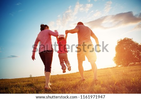 girl with mother and father holding hands on the nature. Child with parents outdoors #1161971947