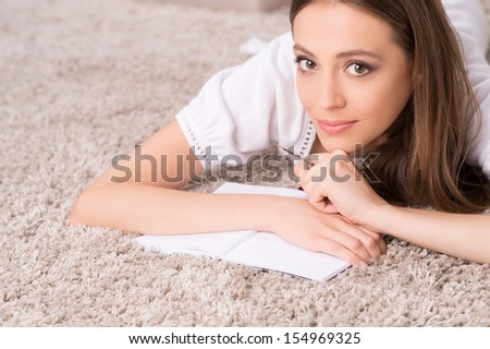 Girl with note pad. Beautiful young woman lying on the floor and writing something in her note pad
