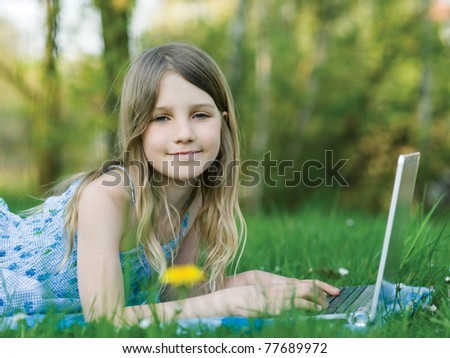 Girl with notebook computer on green meadow