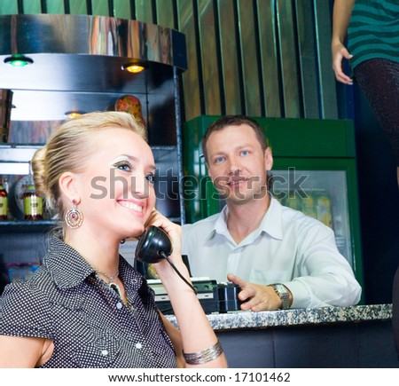 girl with old phone in a bar