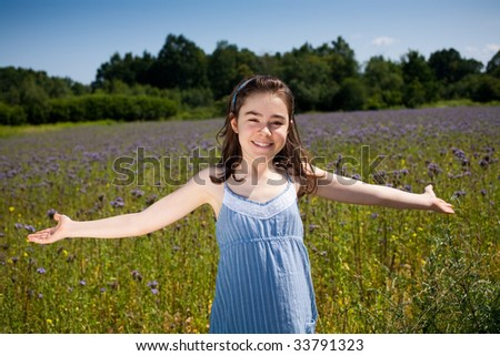Girl with open arms against green meadow - stock photo