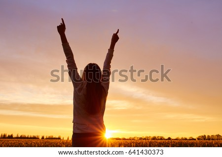Girl with open arms on a green wheat field in the morning #641430373