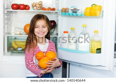 girl with oranges on background refrigerator