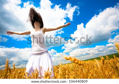Girl with outstretched arms is enjoys summer day in the yellow field