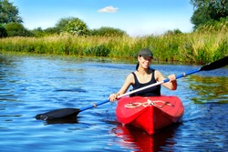 Girl with paddle and kayak on a small river in rural landscape