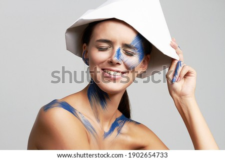 Girl with paint on her Face. Blue paint on beautiful face and Body. Paper Hat
