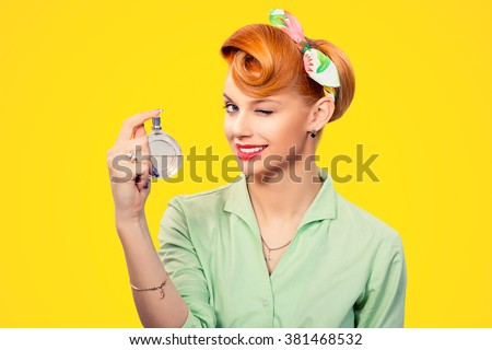 Girl with perfume. Closeup red head beautiful young woman pretty smiling pinup girl green button shirt holding bottle of perfume and smelling aroma looking at you camera, retro vintage 50's hairstyle