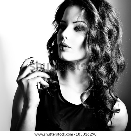 Girl with perfume, young beautiful woman holding bottle of perfume and smelling aroma. Black and white.