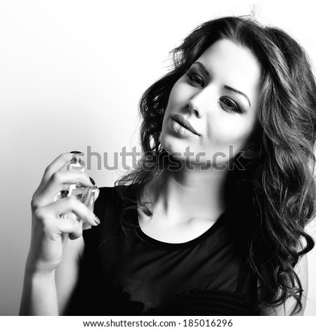 Girl with perfume, young beautiful woman holding bottle of perfume and smelling aroma, black and white.