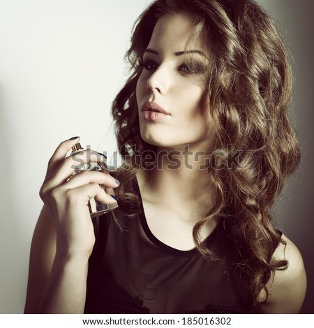 Girl with perfume, young beautiful woman holding bottle of perfume and smelling aroma, toned.