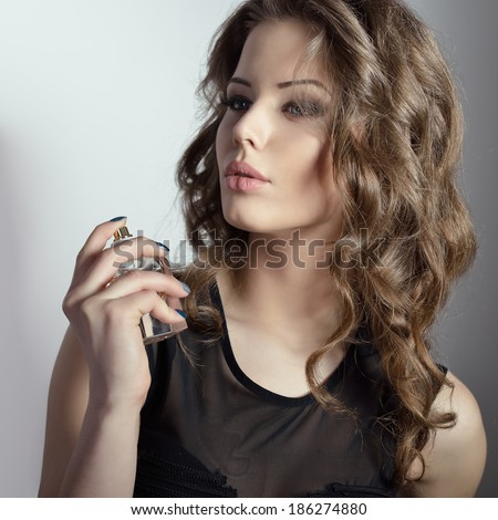 Girl with perfume, young beautiful woman holding bottle of perfume and smelling aroma. Toned.